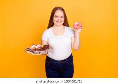Concept of having dependency on fast unhealthy products. Excited smiling woman  she is holding a plate with confectionery and showing funny glazed with frosting donut isolated on yellow background