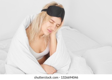 The concept of a headache in the morning, insomnia, hangover. A young beautiful woman holding her head with an expression of pain on her face on a white bed.
