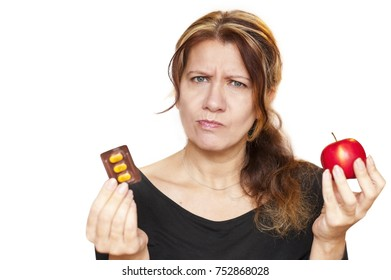 Concept of health. Middle-aged woman with an apple in one hand and pills in the other hand. She has a surprised look. She chooses what is the best - fruits or pills. Isolated