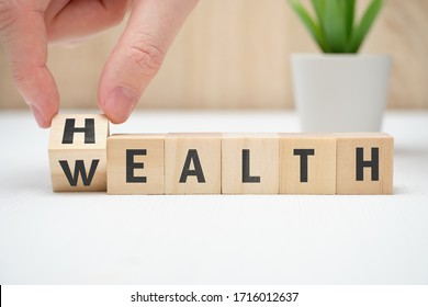 Concept health wealth on wooden block hold hand. Close up.