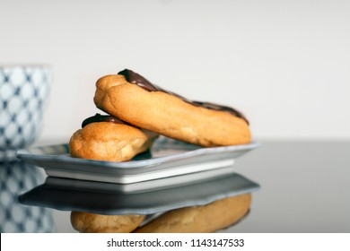 Concept Health without trans fat. Choux   or traditional french eclairs with chocolate ganache, select focus and blurred background. Frozen chocolate covered eclair at tea time.