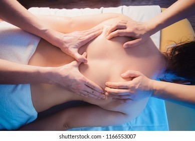 Concept of healthcare and female beauty. Two masseuses make a double back massage of a girl in a spa salon. hands view