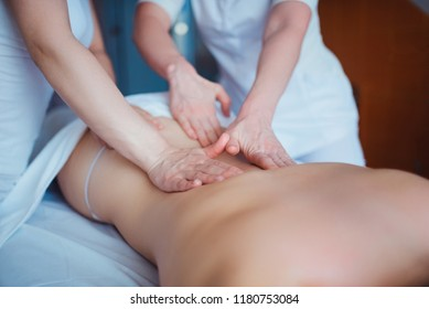 Concept of healthcare and female beauty. Two masseuses make a double back massage of a girl in a spa salon. Four hands of the masseur during the massage close