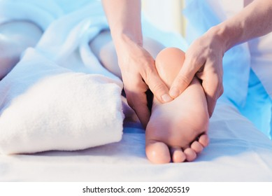 Concept of healthcare and female beauty. Two masseuses make a double legs and feet massage of a girl in a spa salon. Four hands of the masseur during feet massage view