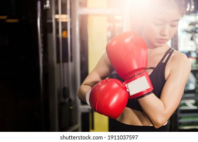 Concept of health-loving woman. Female boxer wearing red boxing gloves in fitness gym.