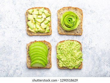 Concept of healthy breakfast toasts with avocado smashed, slices, chunks and rose. Different ways of making and serving delicious avocado sandwich, top view, white stone background, close-up