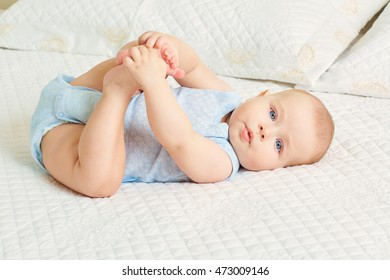 The concept of a healthy child. Cute baby boy with blue eyes lying on her back in the room on the bed, holding her legs with his hands.