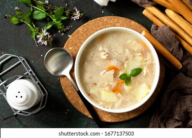 The concept of a healthy and diet food, tasty soup with chicken, cream cheese and cereals on a dark stone table. Top view flat lay background.