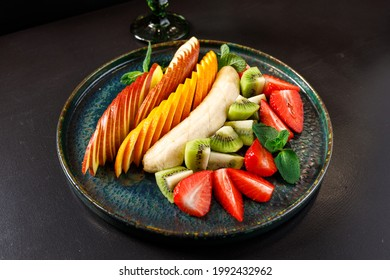 The concept of a healthy diet. Platter fruits and berries - apple, orange, banana, kiwi, strawberry, mint