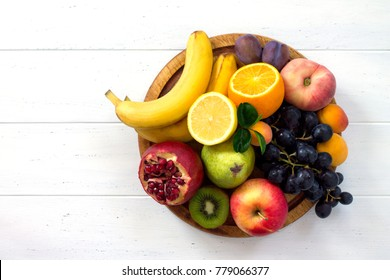 The concept of a healthy diet. Platter fruits and berries - orange, pear, apple, pomegranate, grapes, peach, apricot. Vegan cuisine. Flat lay. Top view.