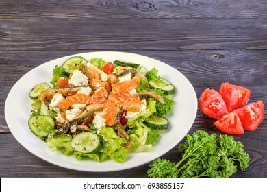 The concept of healthy diet. Salad of smoked salmon and smoked eel, with vegetables and lettuce leaves. On a dark wooden background.