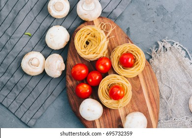 concept Healthy eating. Ingredients for vegetarian Salad of Vegetables: pasta with Cherry Tomatoes and mushrooms on a concrete background. top view or close up