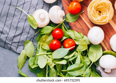 concept Healthy eating. Ingredients for vegetarian Salad of Vegetables: pasta with Cherry Tomatoes and mushrooms, fresh spinach on a concrete background. top view or close up