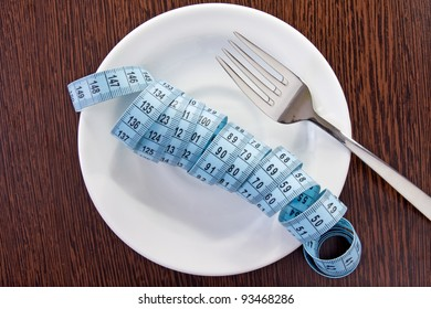concept for healthy eating. plate with measuring tape and fork
