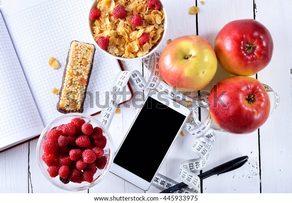 Concept of healthy food, accessories for recording diet: a smartphone, notebook, pen and measuring tape. Juicy berries and apples on a wooden table.