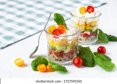 Concept of healthy food, clean eating, low calories delicious meal. Salad with quinoa and fresh vegetables with olive oil in glass jar.  Zero waste no plastic. Close up wooden background copy space