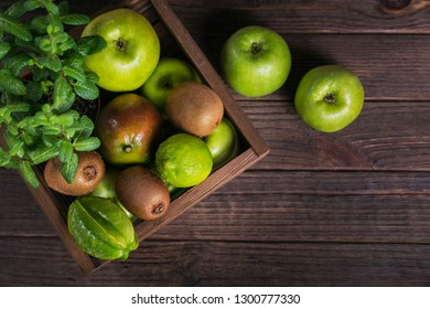 Concept of healthy food. Fresh green fruits in box on dark wooden background. Set of green fruits for healthy diet and detox: apple, lime, kiwi, mango, carambola and mint. Flat lay