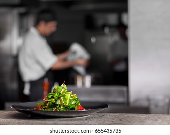 Concept of healthy food. Fresh spring green salad with lettuce, pomegranate and grapefruit, in black plate. Chef working in the dark background interior of modern restaurant kitchen. Ready to eat.