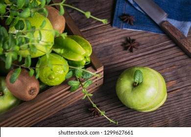 Concept of healthy food. Sliced green apple on cutting board and fresh green fruits in a box. Dark wooden background. Set of green fruits for healthy diet and detox: apple, lime, carambola and mint.