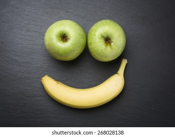 "Concept ""healthy is good"": Smiley face with fresh apples and banana looking happy and smiling, isolated on dark grey stone plate."