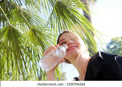 The concept of a healthy life. A girl sitting on a sunny day under a palm tree smiles and drinks water