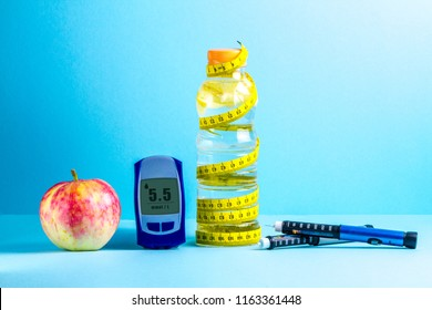 Concept of a healthy lifestyle. Detox water, glucose meter, apple, pen for insulin injection, measuring tape and sneakers on a blue background. Diabetes. Sports life of a diabetes patient.