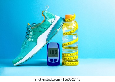 Concept of a healthy lifestyle. Diabetes. Sugar diabetes. Sports diabetics. Detox water, glucose meter, measuring tape and sneakers on a blue background.