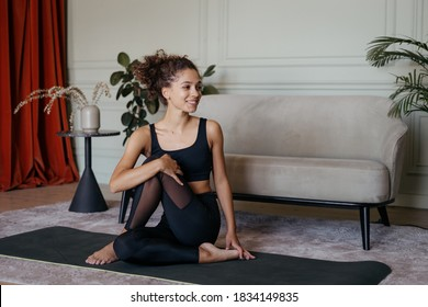 Concept of healthy lifestyle. Happy and adult african american woman training at home, sitting on sport mat, making exercise, smiling wide and stretching upper body