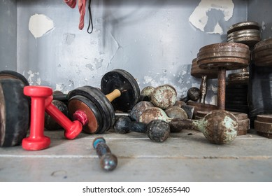 Concept - healthy lifestyle. Old retro dumbbells are lying on the floor in a boxing gym, sports gear, copyspace