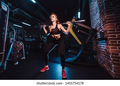 The concept of a healthy lifestyle and workouts in the gym. Blonde girl in sportswear engaged in a gym and does the sitting down with a barbell. bottom point from the front close up view