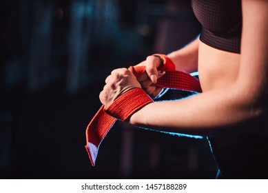 The concept of a healthy lifestyle and workouts in the gym. Blonde girl in sportswear engaged in the gym and does deadlift with a barbell. getting ready for exercise putting on safety ropes close