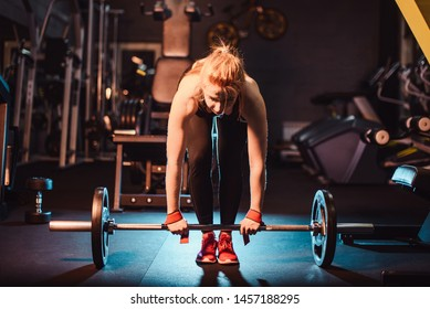 The concept of a healthy lifestyle and workouts in the gym. Blonde girl in sportswear engaged in the gym and does deadlift with a barbell from the front