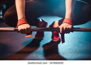 The concept of a healthy lifestyle and workouts in the gym. Blonde girl in sportswear engaged in the gym and does deadlift with a barbell close up view