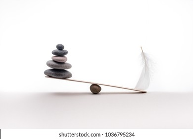 Concept of heavy and light. Meditation stones and plume isolated on white background.