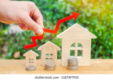 concept of high demand for real estate. population growth. increase in the cost of utilities. property. rise in house prices. wooden houses from small to large with a red arrow up.