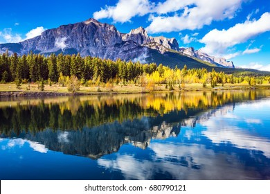 Concept hiking. Canmore, near Banff. Red-orange trees and jagged mountains are reflected in the  lake