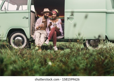 Concept of hippie lifestyle and rest. Full length portrait of smiling ethnicity lady looking at mobile phone with hipster male lover while sitting in retro van with cup of coffee