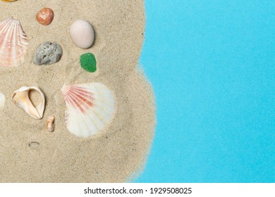The concept of a holiday by the sea, vacation planning. Top view. Fine sand with pebbles, shells and colored glass on a blue background. Copy of the space