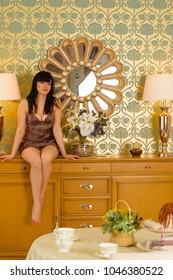 The concept of home comfort. A woman of Hispanic appearance at home in the apartment enjoys a good afternoon or evening
