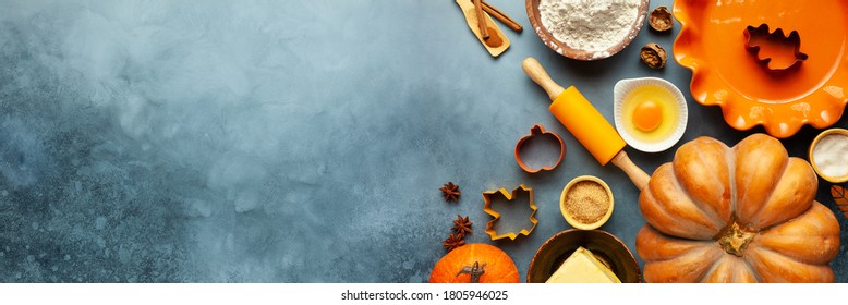 Concept homemade fall baking with pumpkin, food ingredients, spices and kitchen utencil. Cooking pumpkin pie and cookies for Thanksgiving day.