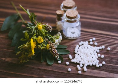 Concept of homeopathy. Various pharmacy bottles of homeopathic medicine on wooden board
