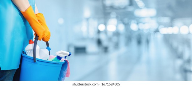 The concept of homework and cleaning. A cleaning lady is standing with a bucket and cleaning products on a blurred background.
