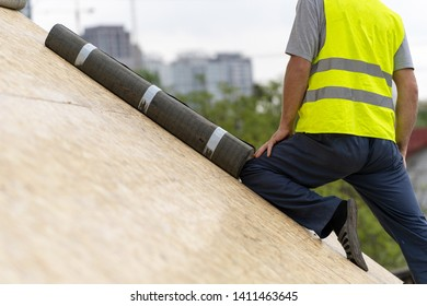 Concept of house under construction. Cropped, unrecognizable, professional and qualified roofer in protective uniform wear standing near waterproof bitumen membrane on rooftop of new modern building