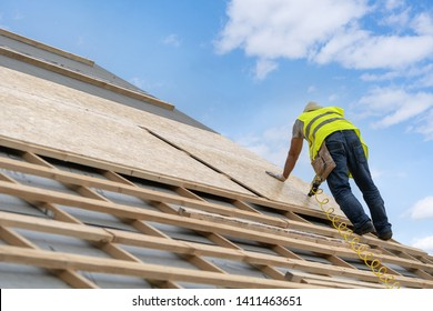 Concept of house under construction. Qualified, unrecognizable and mature contractor in protective work wear holding pneumatic nail gun in hands and fixing roof cover against blue sky on background