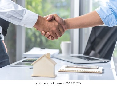 Concept of housing purchase and insurance, two business people estate agent with customer shaking hands after contract signature successful in real estate agency office