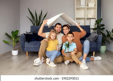 the concept of housing for a young family. Mother father and children in a new house with a roof in the house