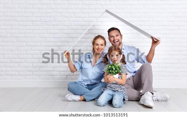 conceito de habitação de uma família jovem. Mãe pai e filho em casa nova com um telhado na parede de tijolos vazia