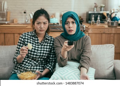 Concept of human reactions. Group of female friends sit on sofa in bright dining room and watching video holding breath. japanese and muslim lady roommates eating chips while horror movie play on tv