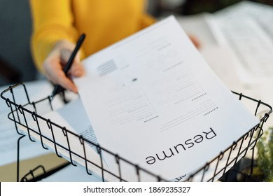 Concept of human resources. Selective focus on resume. Cropped woman working in office, sitting behind desk and pick summary from box with documents to consideration of an application for a job