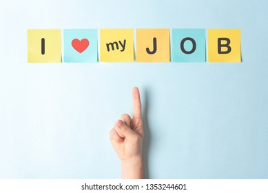 """Concept of """"I love my job"""" using multicolor sticky notes on blue background and a finger pointing up."""